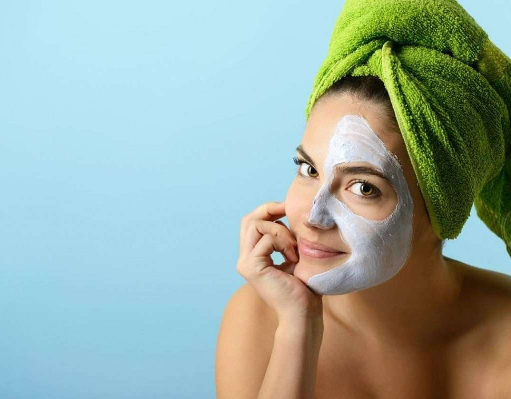 Beautiful young woman with facial mask, beauty treatment over bl