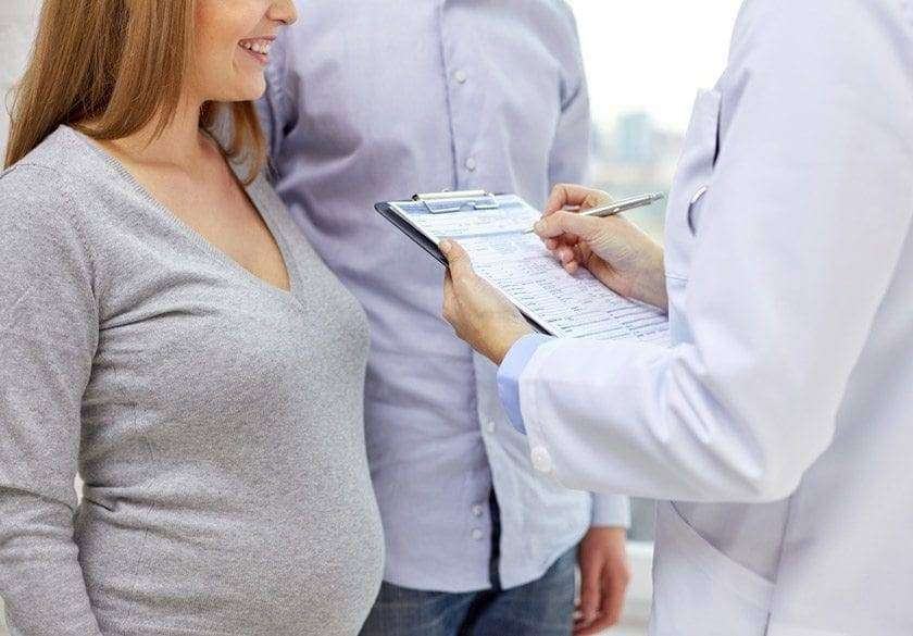 close up of happy pregnant woman and doctor