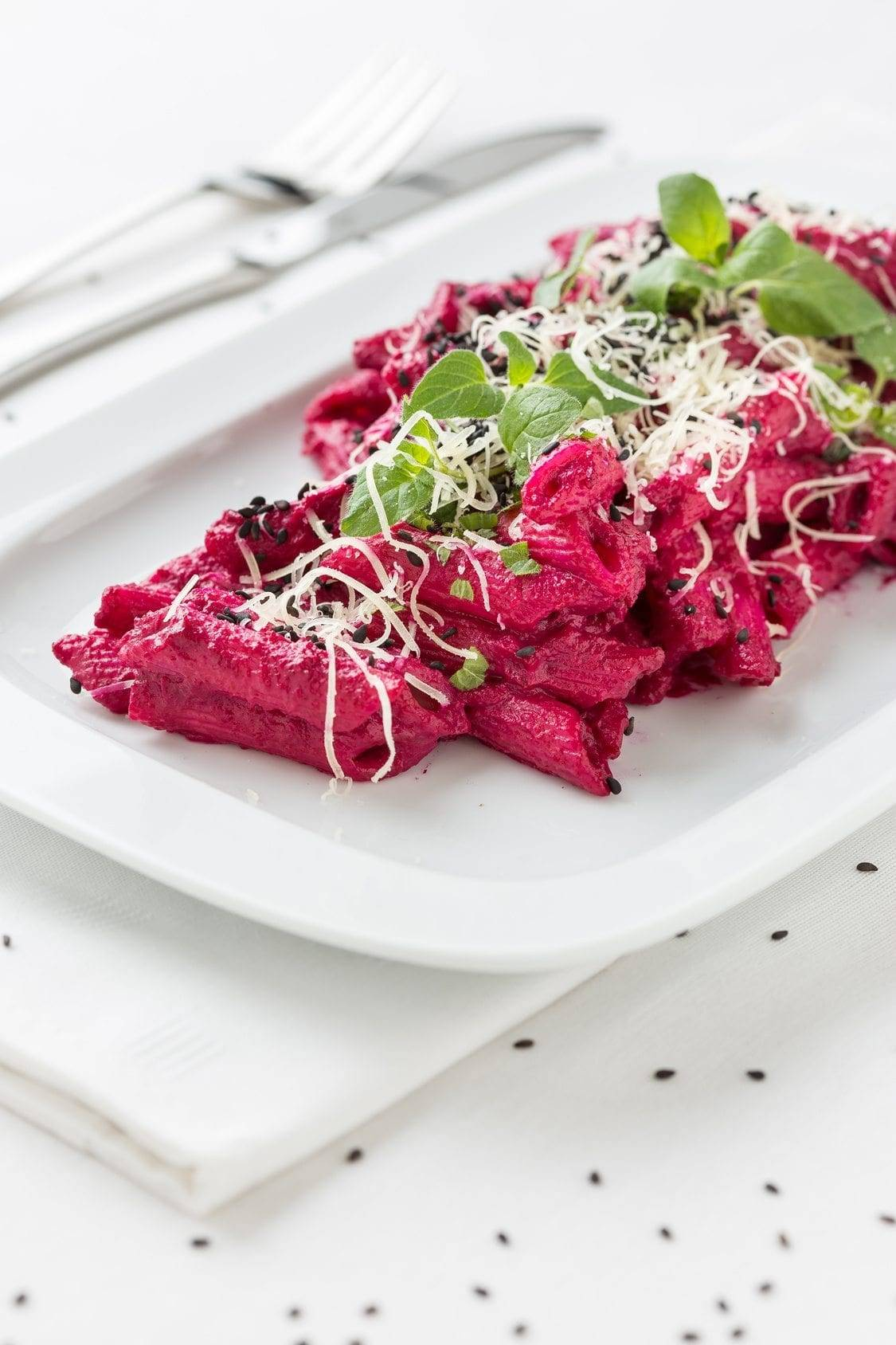 macaroni with red beet sauce on white plate