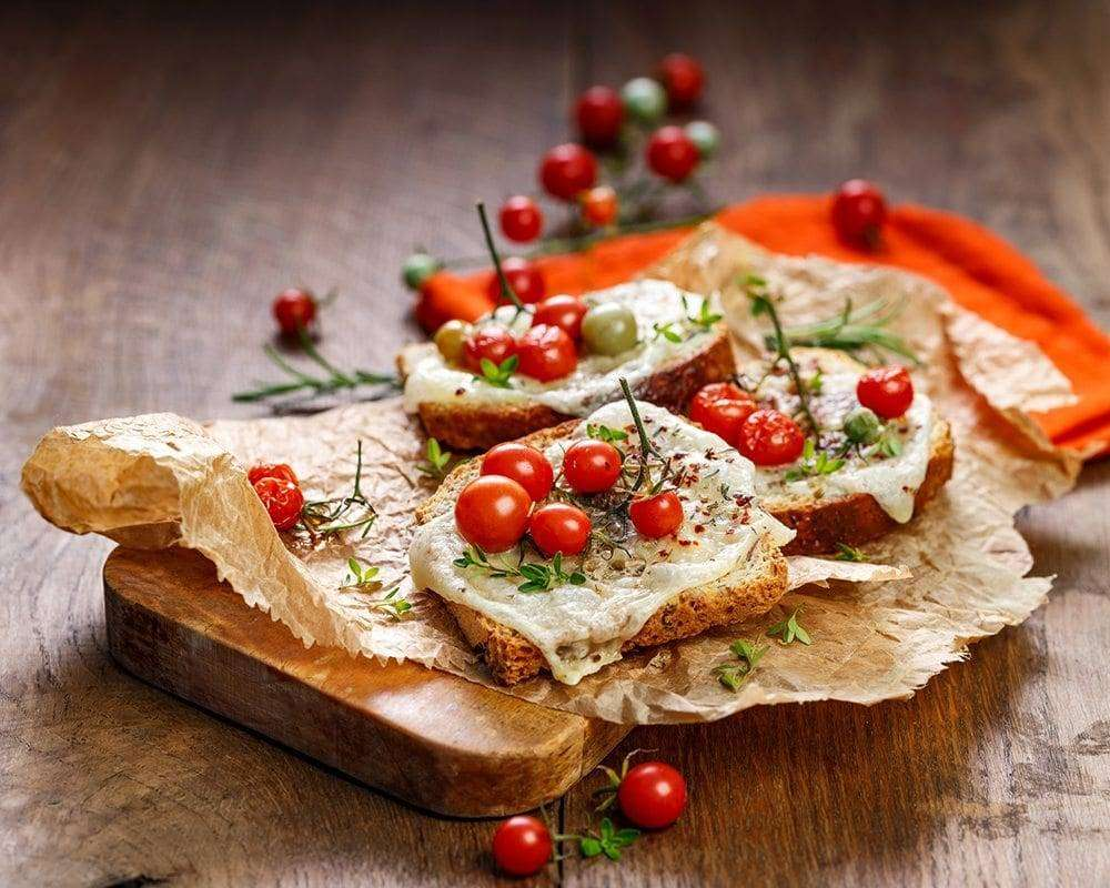 Toast with cheese, cherry tomatoes and aromatic herbs