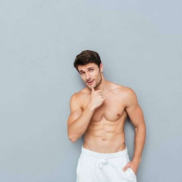 Portrait of handsome shirtless athletic young man over grey background
